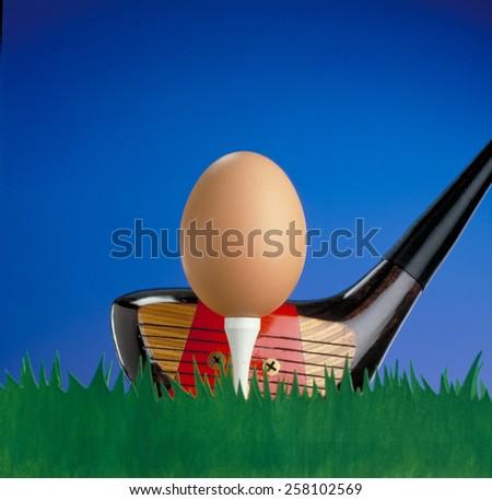Golf club hitting an egg like golf ball.Funny golf concept. - stock photo