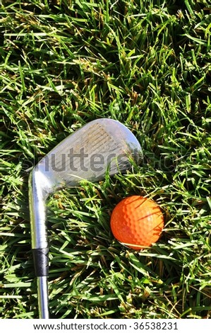 golf club laying on grass with orange ball room for your text - stock photo