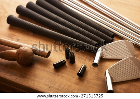 Golf club making. Golf club components on a work desk or work bench. grips, shaft, ferrules  and, iron head.Focus is on black ferrule parts. Shallow depth of field. - stock photo
