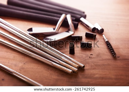 Golf club making. Golf club components on a work desk or work bench. intentionally shot in impression-like surreal color. Focus is on black ferrule parts. - stock photo