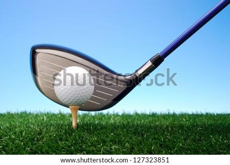 Golf club ready to drive golf ball on tee - stock photo