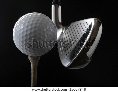 Golf club with ball on a tee in the black background