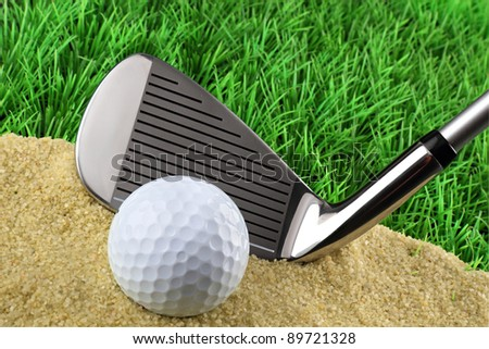 golf club with ball on sand in front of the green - stock photo