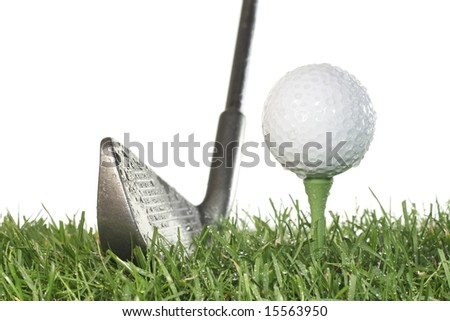 Golf club with golf ball on a tee and grass on a white background in damp conditions. - stock photo