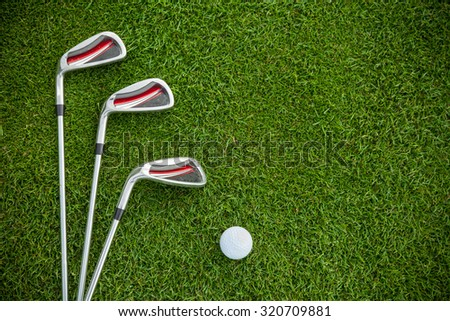 Golf clubs and ball in grass, shot from aerial view - stock photo