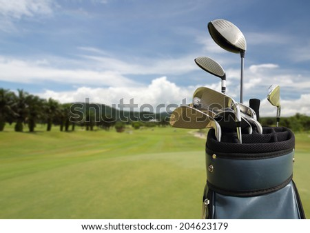 Golf clubs drivers over green field background  - stock photo