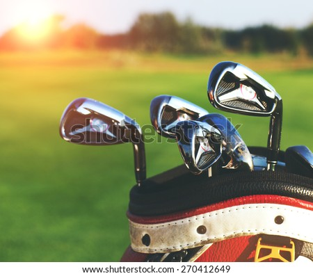 Golf clubs drivers over green field background. Summer sunset - stock photo