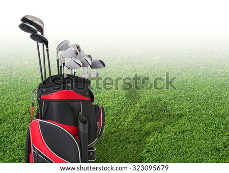 Golf clubs in a red and black bag in front of faded tee box grass - stock photo