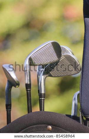 Golf clubs in bag against an autumn foilage background - stock photo