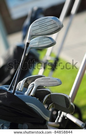 Golf clubs in golfbag, green grass background - stock photo