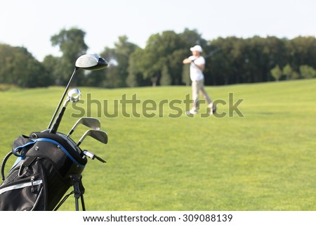 Golf clubs in golfbag isolated on green grass background. Man in light clothes playing professional golf game on the background.