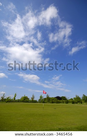 Golf cours with blue and cloudy sky - stock photo