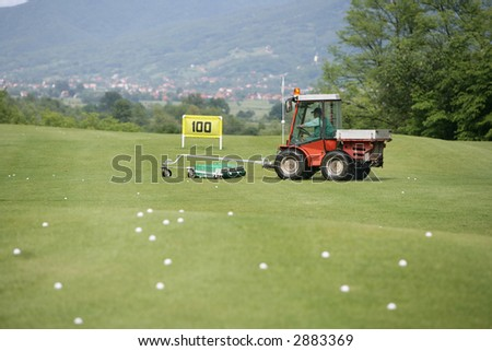 Golf course and a vehicle collecting balls - stock photo