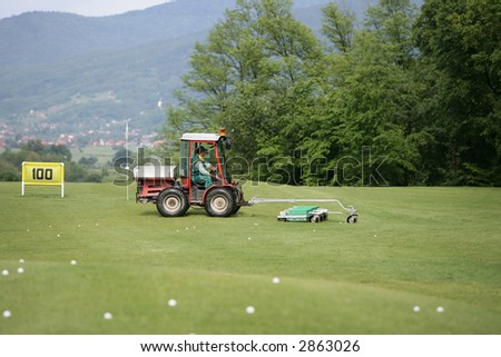 Golf course and a vehicle collecting golf balls - stock photo