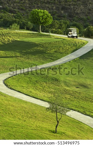 Golf course during sunrise with golf car