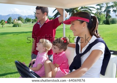 golf course family father mother and daughters in buggy green grass field - stock photo