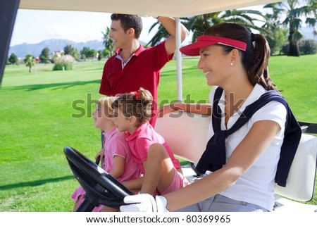 golf course family father mother and daughters on buggy in a green grass field - stock photo