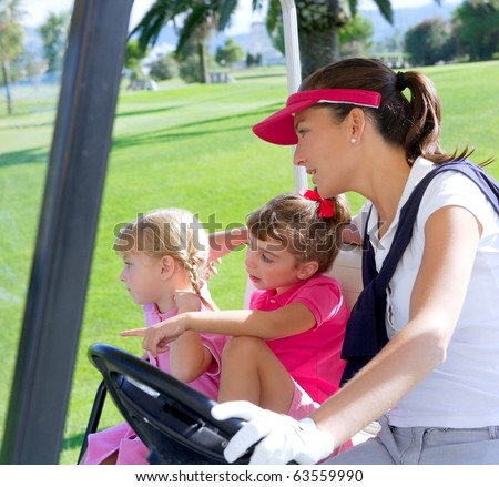 golf course family mother and daughters in buggy green grass field - stock photo