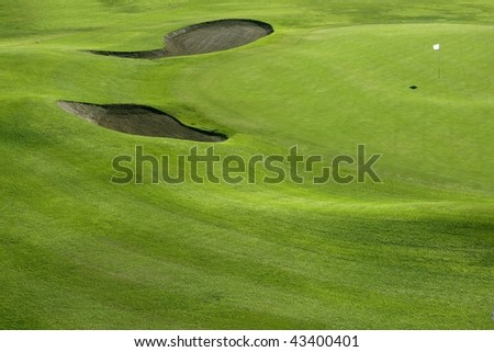 Golf course green grass hill field with holes and flag - stock photo