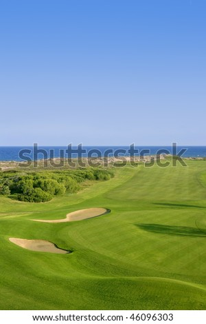 Golf course green grass, sea ocean and summer blue sky - stock photo