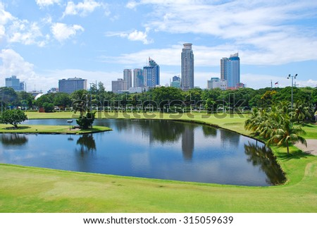 Golf Course Green with City Background - stock photo