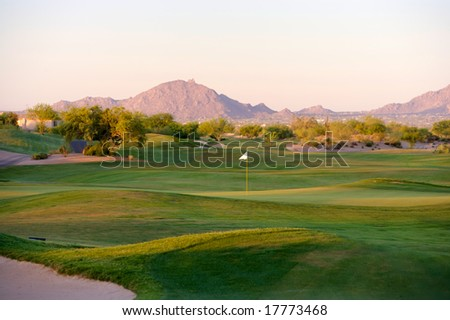 Golf course in the Arizona desert with mountains in the late afternoon sun - stock photo
