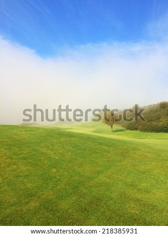Golf course in the morning mist - stock photo