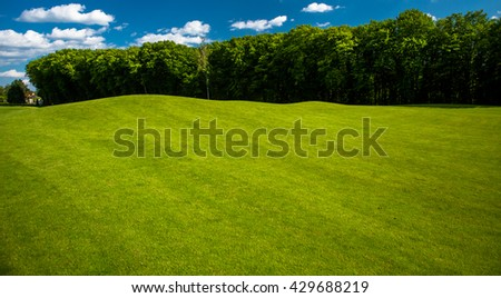 Golf course landscape in spring or summer time. Field for playing golf. Nice nature and environment with blue sky and white clouds. Nobody.