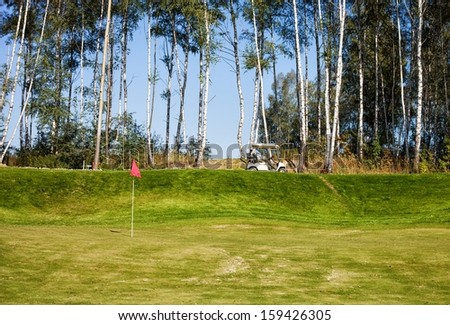 Golf course landscape with green and golf-cart car - stock photo