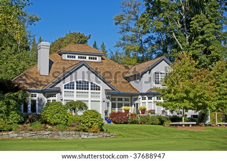 golf course resort home with blue sky & lush landscaping - stock photo
