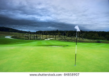 golf course under dramatic cloud sky - stock photo