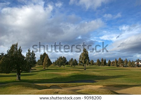golf course with a cloudy blue sky - stock photo