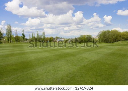 Golf course with golf hole and flag - stock photo