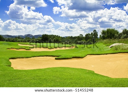 Golf course with green grass, sand traps(bunkers) and flag in the distance with a perfect sky - stock photo