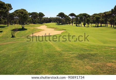 Golf course with sand trap. - stock photo