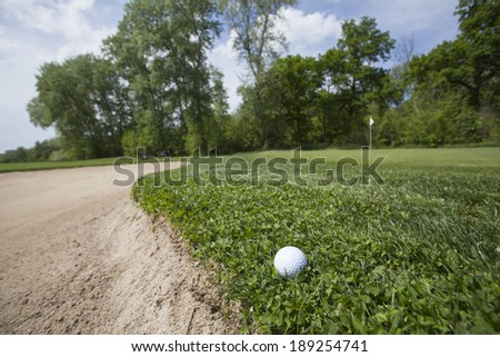 Golf course with the ball in front and beautiful nature in the back