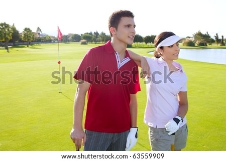 Golf course young happy players couple stand up posing on green