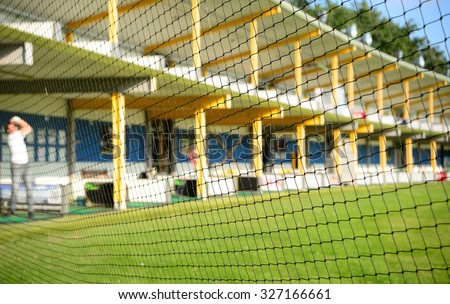 Golf driving range levels from behind protective net. Selective focus on net with blurred background of driving range and players. - stock photo