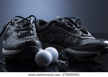 Golf equipment consisting of balls, tees and shoes, isolated on dark blue background. - stock photo