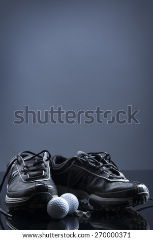 Golf equipment consisting of balls, tees and shoes, isolated on dark blue background with empty copy space for text. - stock photo