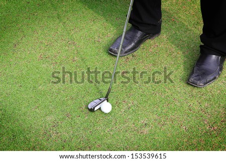 Golf equipment, golf ball with tee on course  - stock photo