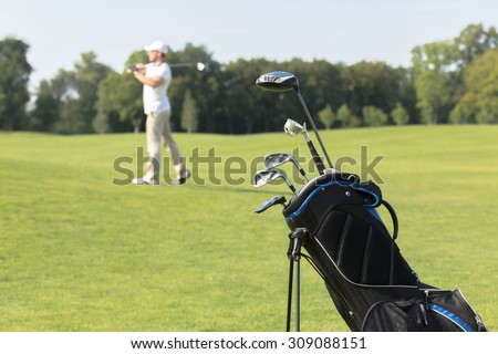 Golf equipment. Golf clubs in golf bag on the foreground, man playing golf on the background during summer vacation.