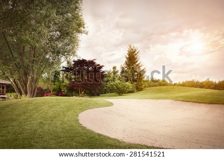 Golf fairway with sand bunker and beautiful sky at sunset. - stock photo