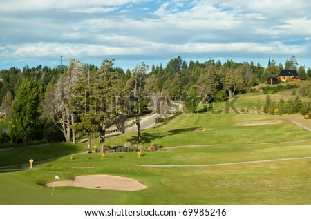 golf field near the road with a house on a hill - stock photo