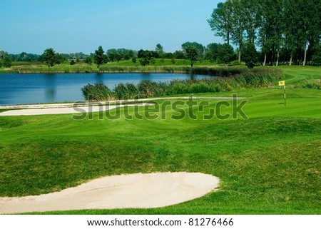 Golf field with green, lake, sand and hole 17 flag - stock photo