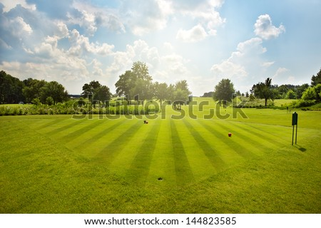 golf field with trees over cloudy blue sky - stock photo