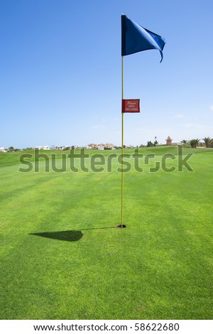 Golf flag in the hole on a course green - stock photo