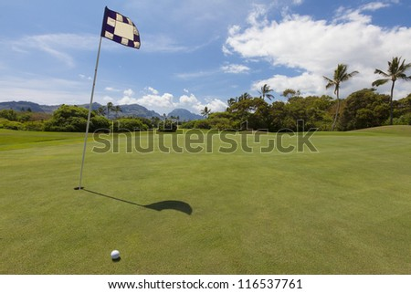 Golf flag indicating the hole on a scenic, smooth golf green on a beautiful golf course. Hills and mountains are visible on the horizon under a blue sky dotted with a few mixed clouds. - stock photo