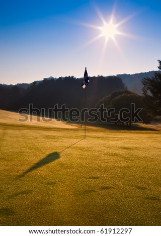 Golf flag on green on clear autumn day - stock photo