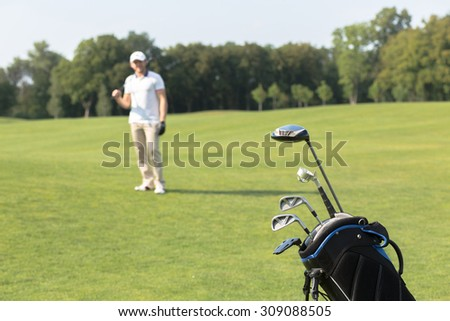 Golf game concept. Golf clubs in bag against the golf course. Golfer standing on the background and holding a driver in his hand.